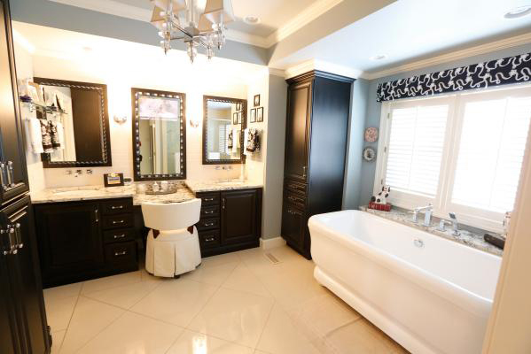 beautiful master bath with dark accent cabinets and bright white tub